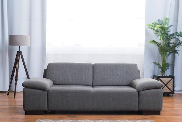 Vista frontal do sofá cinza na sala de estar