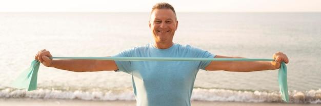 Vista frontal do sorridente homem sênior malhando com corda elástica na praia