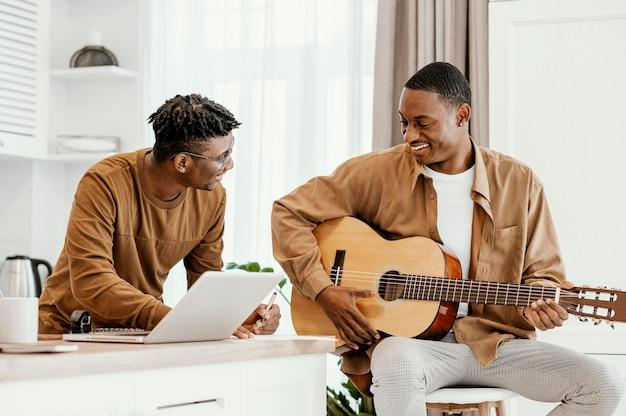 Vista frontal do sorridente músico masculino em casa na cadeira, tocando violão e usando o laptop