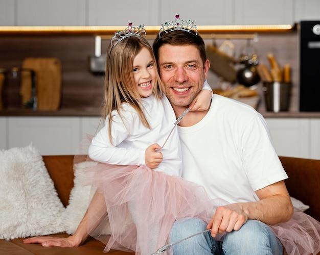 Vista frontal do sorridente pai e filha brincando com a tiara e a varinha juntos