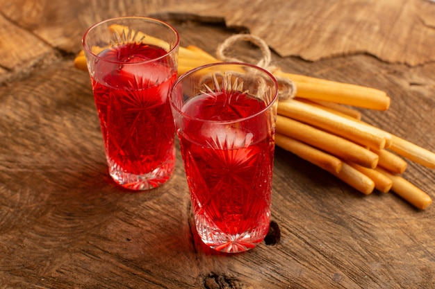 Vista frontal do suco de cranberry vermelho colorido com bolachas de pau na superfície de madeira