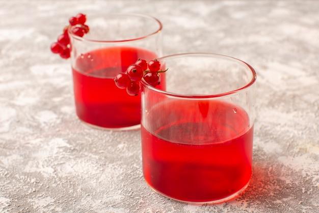 Vista frontal do suco de cranberry vermelho colorido na mesa de luz