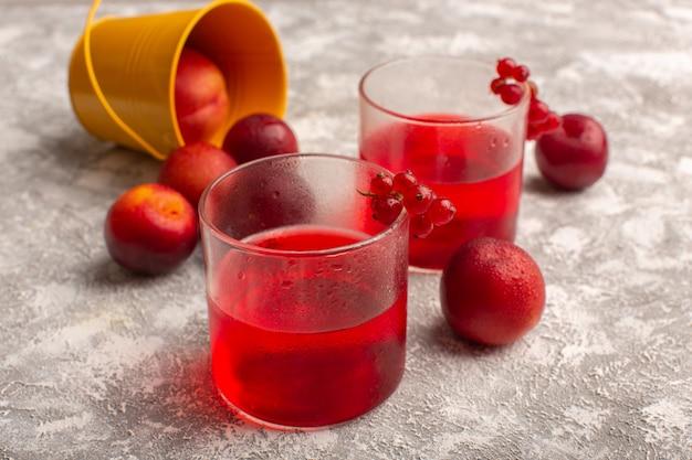 Vista frontal do suco de cranberry vermelho colorido na superfície da luz