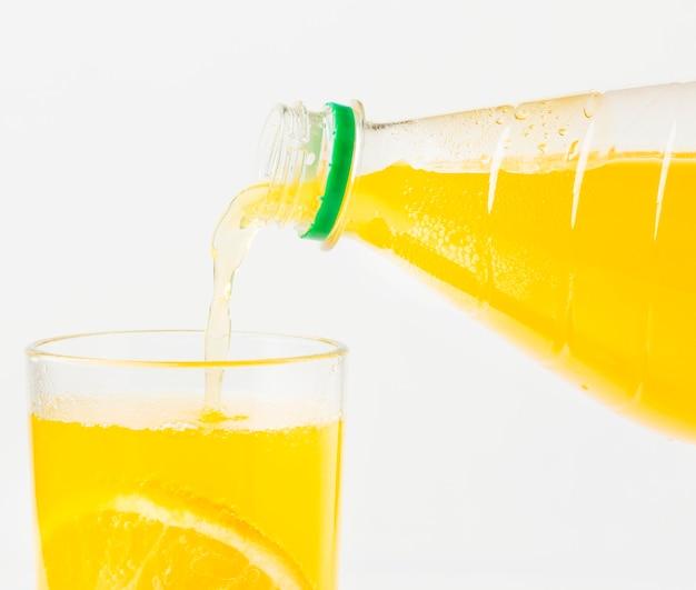 Vista frontal do suco de laranja sendo servido no copo da garrafa
