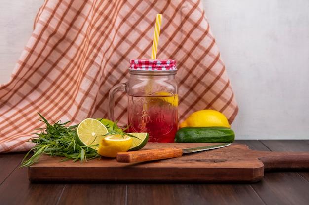 Vista frontal do suco de limão fresco em uma jarra de vidro com limões verdes de estragão em uma placa de cozinha de madeira com faca em uma superfície de toalha de mesa marcada
