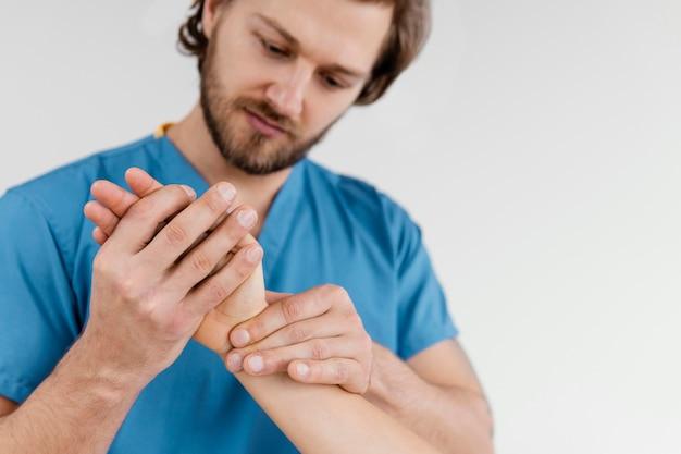 Vista frontal do terapeuta osteopático masculino verificando a articulação do pulso de uma paciente