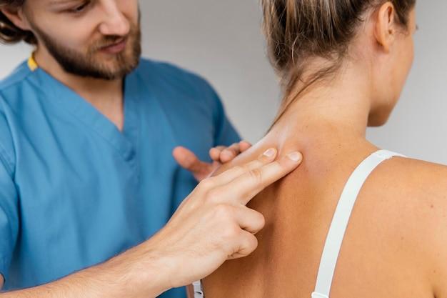 Vista frontal do terapeuta osteopático masculino verificando a coluna vertebral de uma paciente