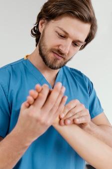 Vista frontal do terapeuta osteopático masculino verificando o pulso de uma paciente