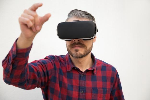 Vista frontal do testador com óculos vr tentando pegar algo