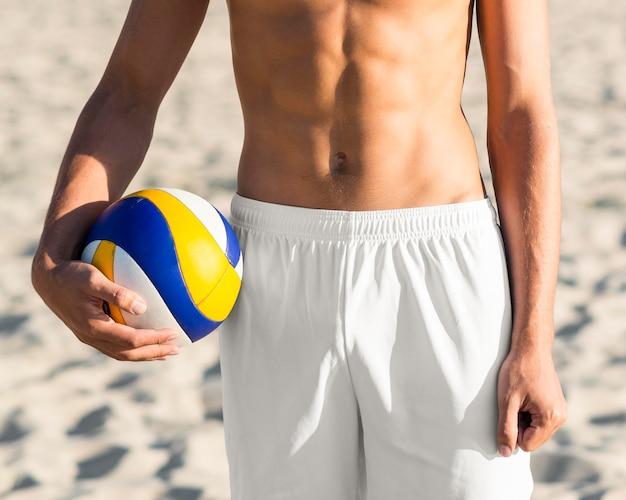 Vista frontal do torso do jogador de vôlei masculino sem camisa segurando uma bola na praia