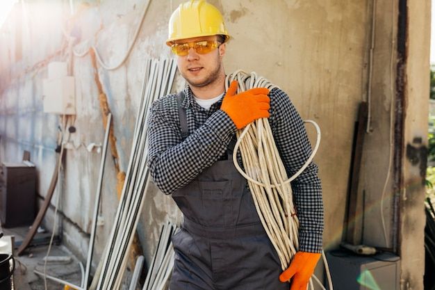 Vista frontal do trabalhador com capacete carregando corda