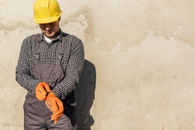 Vista frontal do trabalhador com capacete e espaço de cópia