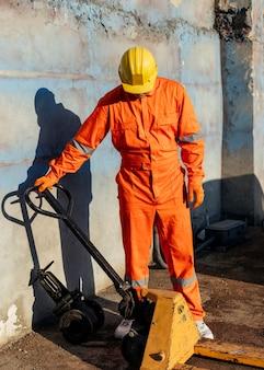 Vista frontal do trabalhador com capacete e uniforme