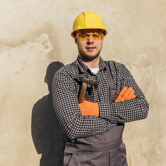 Vista frontal do trabalhador com óculos de proteção e capacete