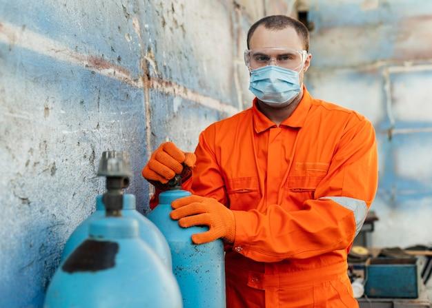 Vista frontal do trabalhador com óculos de proteção e máscara médica