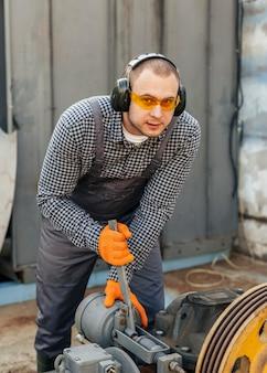 Vista frontal do trabalhador com óculos de segurança e fones de ouvido