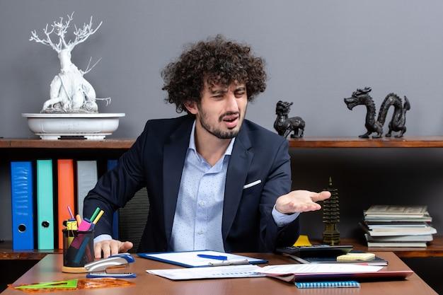 Vista frontal do trabalhador de escritório de processo de trabalho sentado à mesa em um escritório moderno