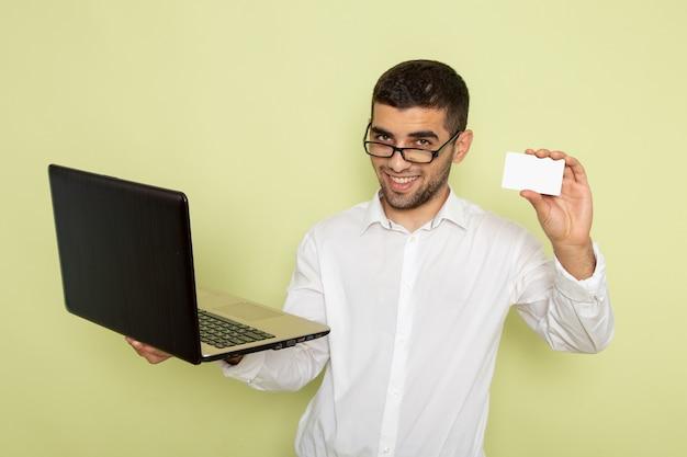 Vista frontal do trabalhador de escritório do sexo masculino com camisa branca, segurando seu laptop e cartão na parede verde