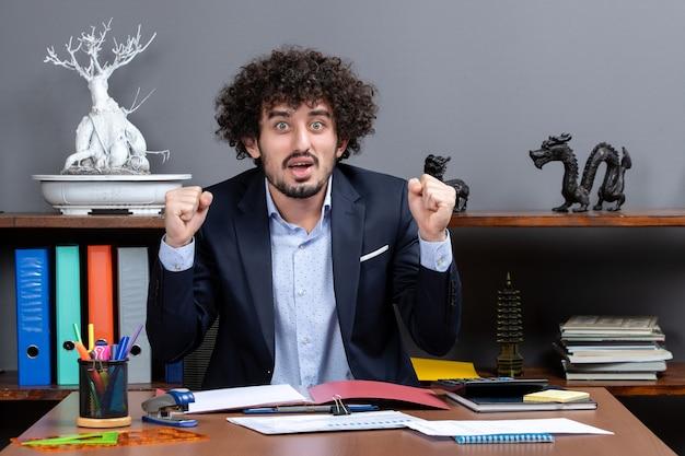 Vista frontal do trabalhador de escritório feliz mostrando gesto vencedor sentado à mesa no escritório