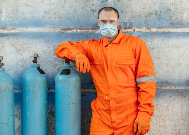 Vista frontal do trabalhador de uniforme com máscara facial e óculos de proteção