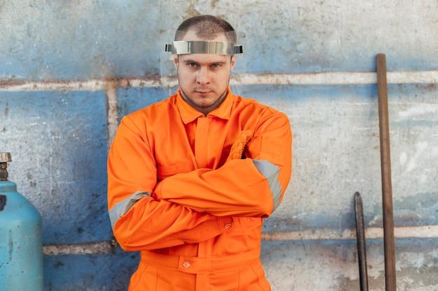 Vista frontal do trabalhador de uniforme com protetor facial