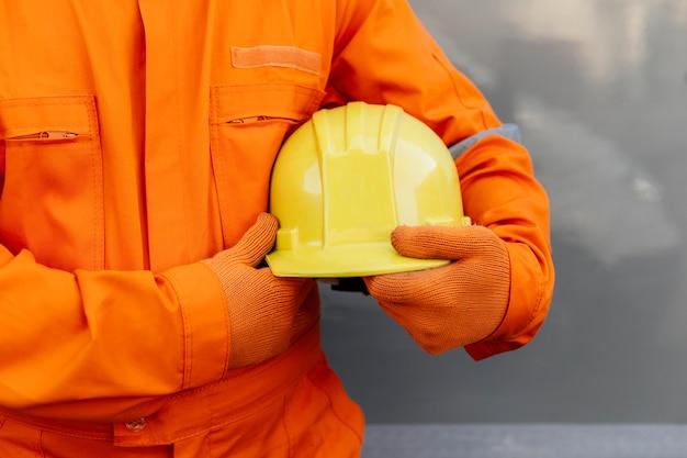 Vista frontal do trabalhador de uniforme segurando capacete