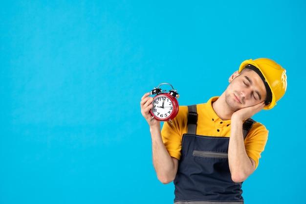 Vista frontal do trabalhador masculino cansado em uniforme amarelo com relógios em azul