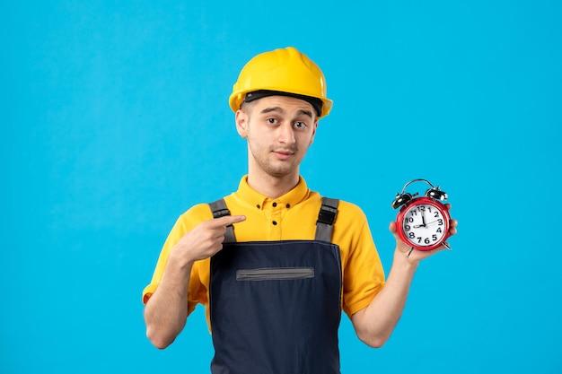 Vista frontal do trabalhador masculino de uniforme apontando para os relógios no azul