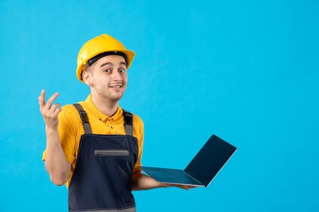 Vista frontal do trabalhador masculino de uniforme com laptop azul