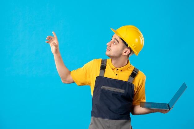 Vista frontal do trabalhador masculino de uniforme com laptop olhando de lado em azul