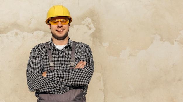 Vista frontal do trabalhador masculino de uniforme com luvas de proteção e espaço de cópia