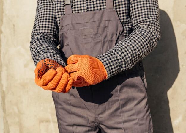 Vista frontal do trabalhador masculino de uniforme com luvas de proteção