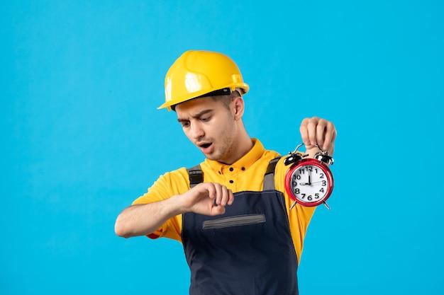 Vista frontal do trabalhador masculino de uniforme com relógios em azul