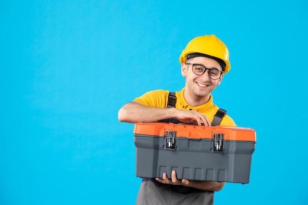 Vista frontal do trabalhador masculino de uniforme e capacete com caixa de ferramentas em suas mãos no azul