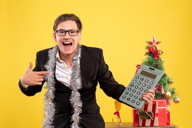 Vista frontal do trabalhador masculino em pé e segurando calculadora