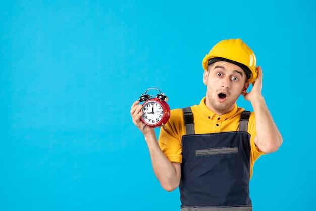 Vista frontal do trabalhador masculino surpreso de uniforme com relógios em azul