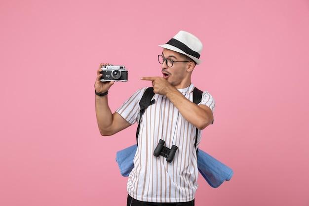 Vista frontal do turista masculino segurando a câmera na parede rosa emoção turista cor