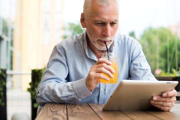 Vista frontal do velho olhando para um tablet