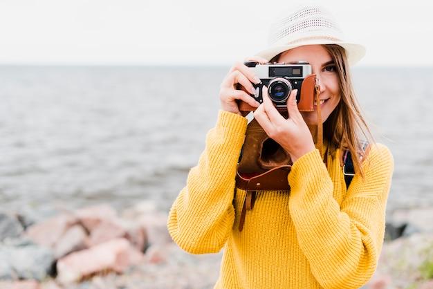 Vista frontal do viajante solitário tirando uma foto