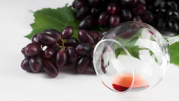 Vista frontal do vinho em um copo e uvas