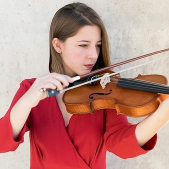 Vista frontal do violinista feminino tocando