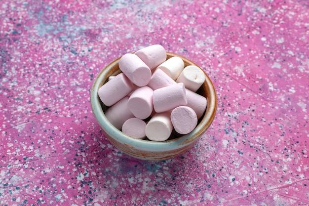 Vista frontal doce deliciosos marshmallows pouco formados dentro do pote redondo na mesa rosa.