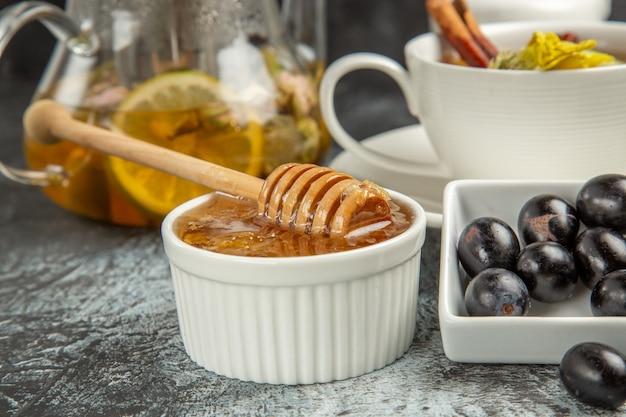 Vista frontal, doce mel com chá e azeitonas na superfície escura, café da manhã
