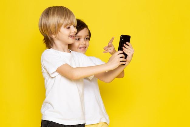 Vista frontal dois meninos adorável fofo tomando selfie sorrindo em amarelo