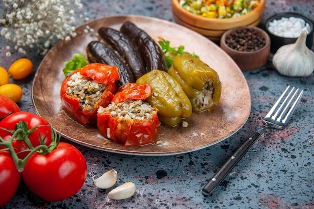 Vista frontal dolma de berinjela com tomate cozido e pimentão recheado com carne moída dentro do prato sobre fundo azul