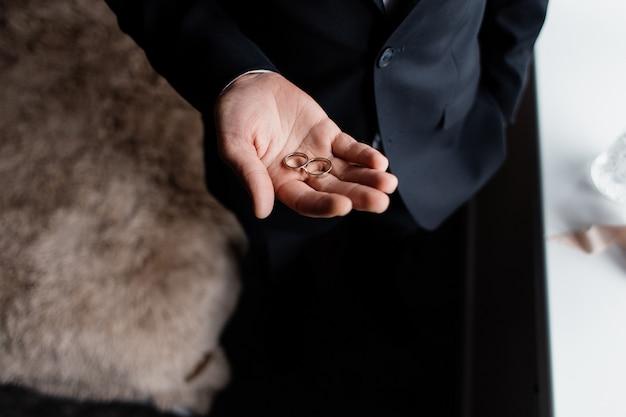 Vista frontal dos anéis de casamento na palma da mão de um noivo