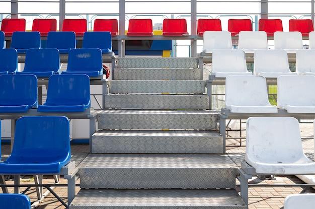Vista frontal dos assentos plactic azuis e vermelhos na arquibancada do estádio de esporte com degraus de metal