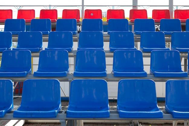 Vista frontal dos assentos plactic azuis e vermelhos na arquibancada do estádio de esporte
