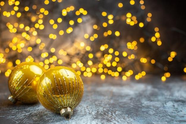 Vista frontal dos brinquedos da árvore de natal com luzes amarelas na foto claro-escuro na cor do ano novo de natal