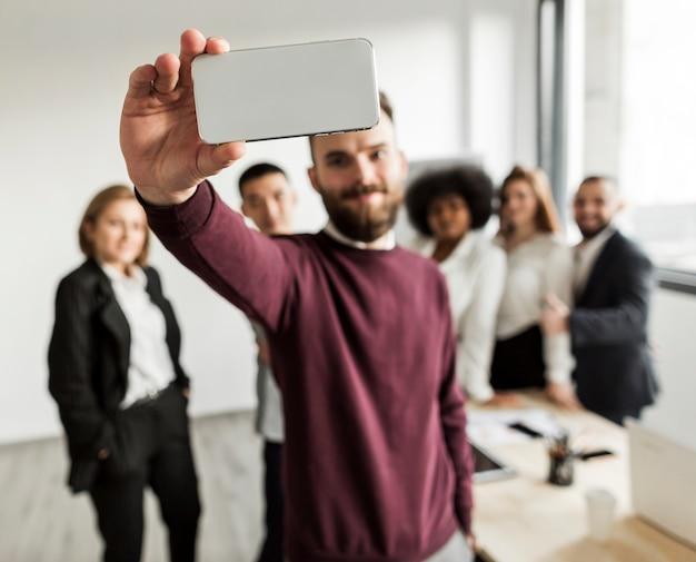 Vista frontal dos colegas tomando uma selfie